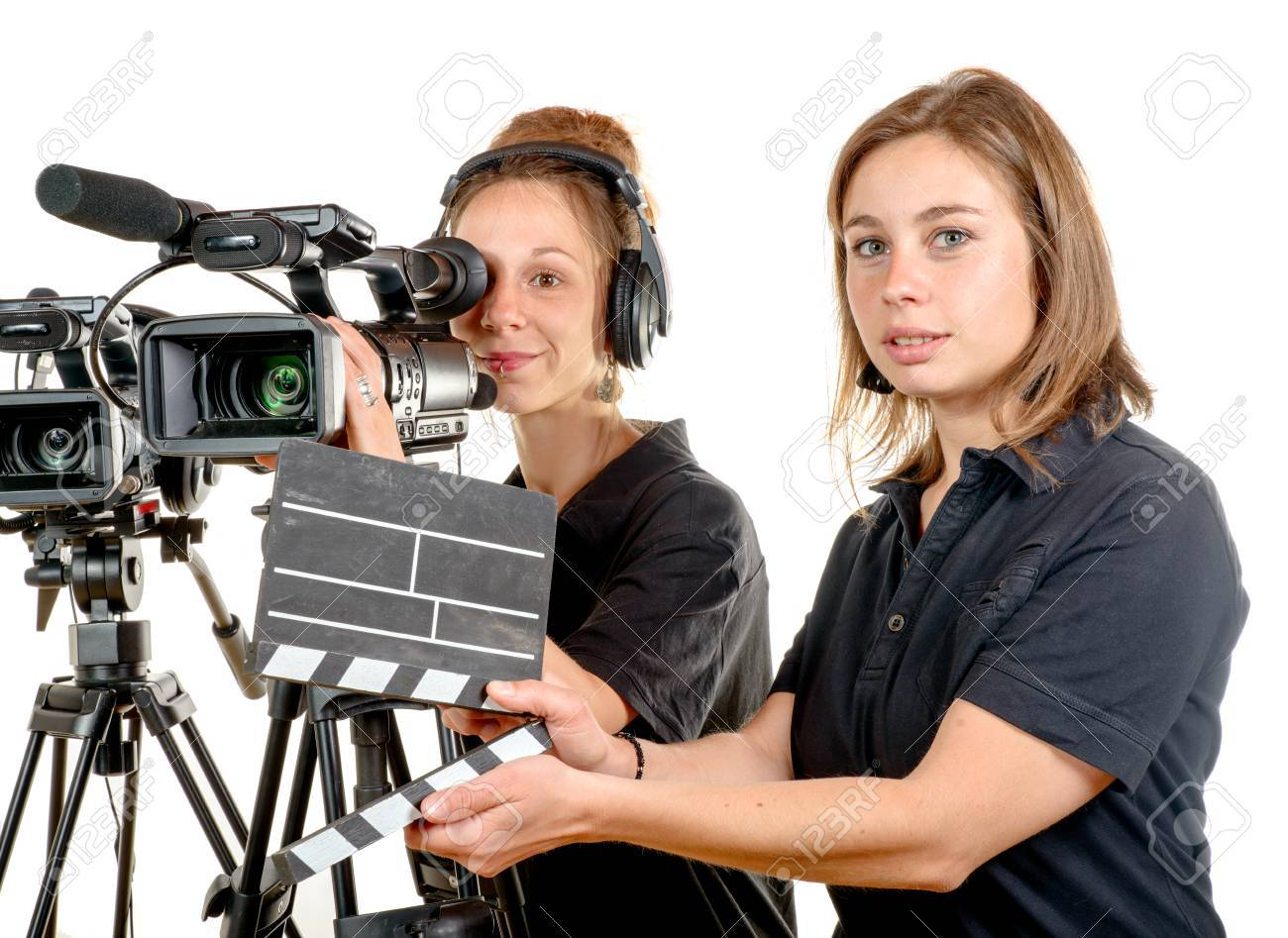 Stock Photo - two pretty young women work with a video camera on the white  background 984f9ce562