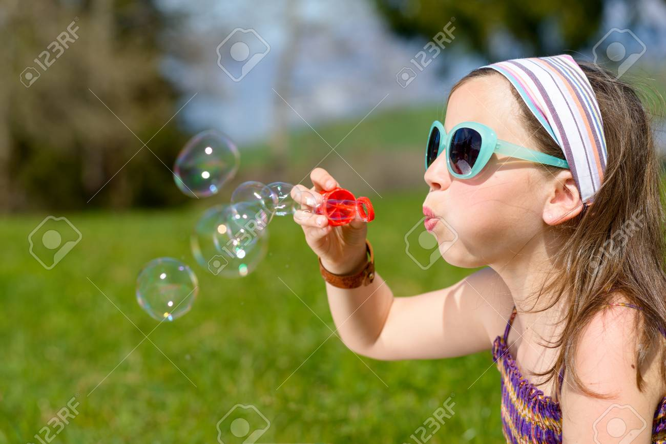 A Little Girl Making Soap Bubbles In Nature Stock Photo Picture And