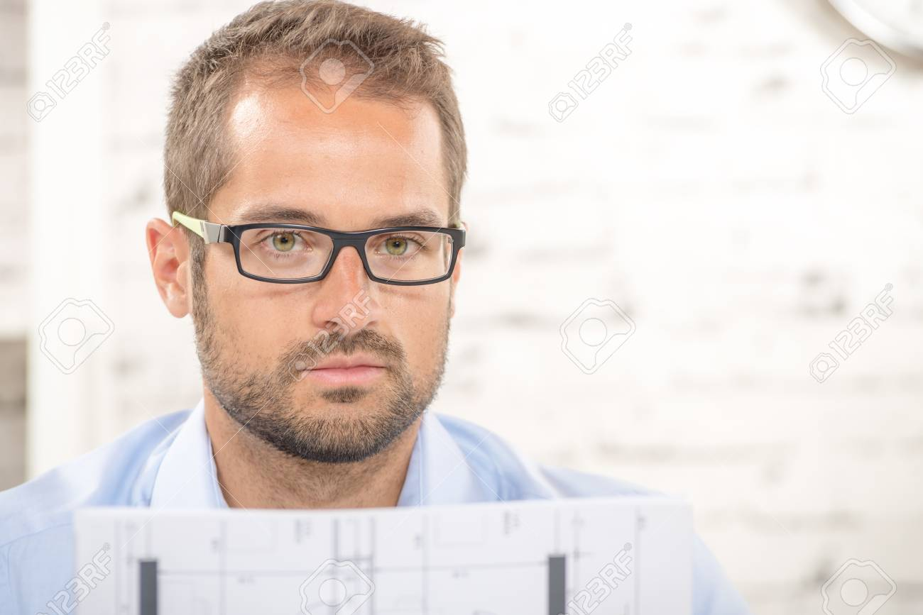 ea64f1623cb a young man with eyeglasses reads a plan Stock Photo - 43625803