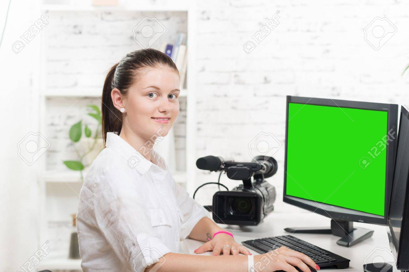 pretty young woman video editor with green screen - 43625810