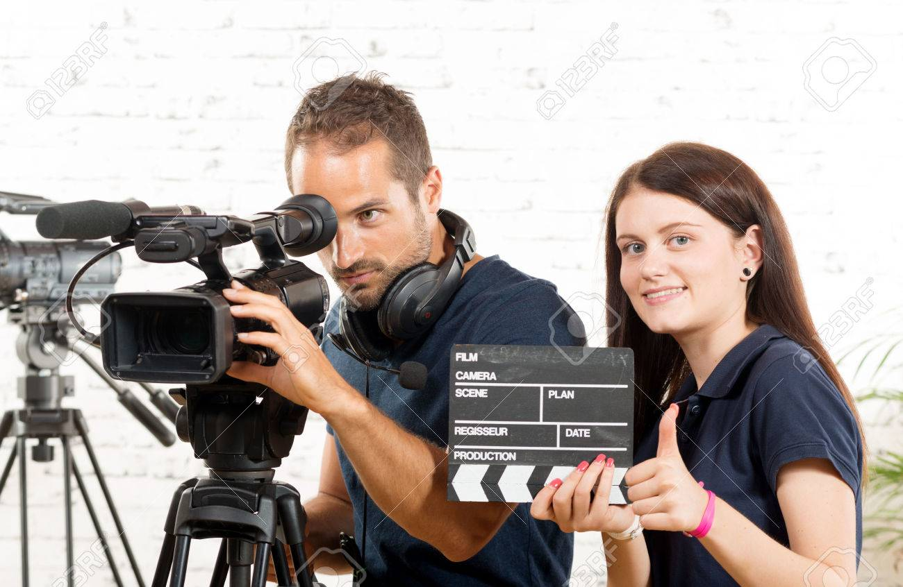 a cameraman and a young woman with a movie camera - 44504998