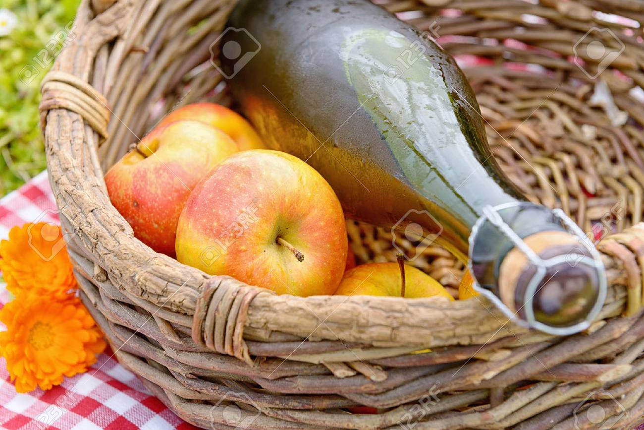 a bottle of cider with apples in a basket - 57594774
