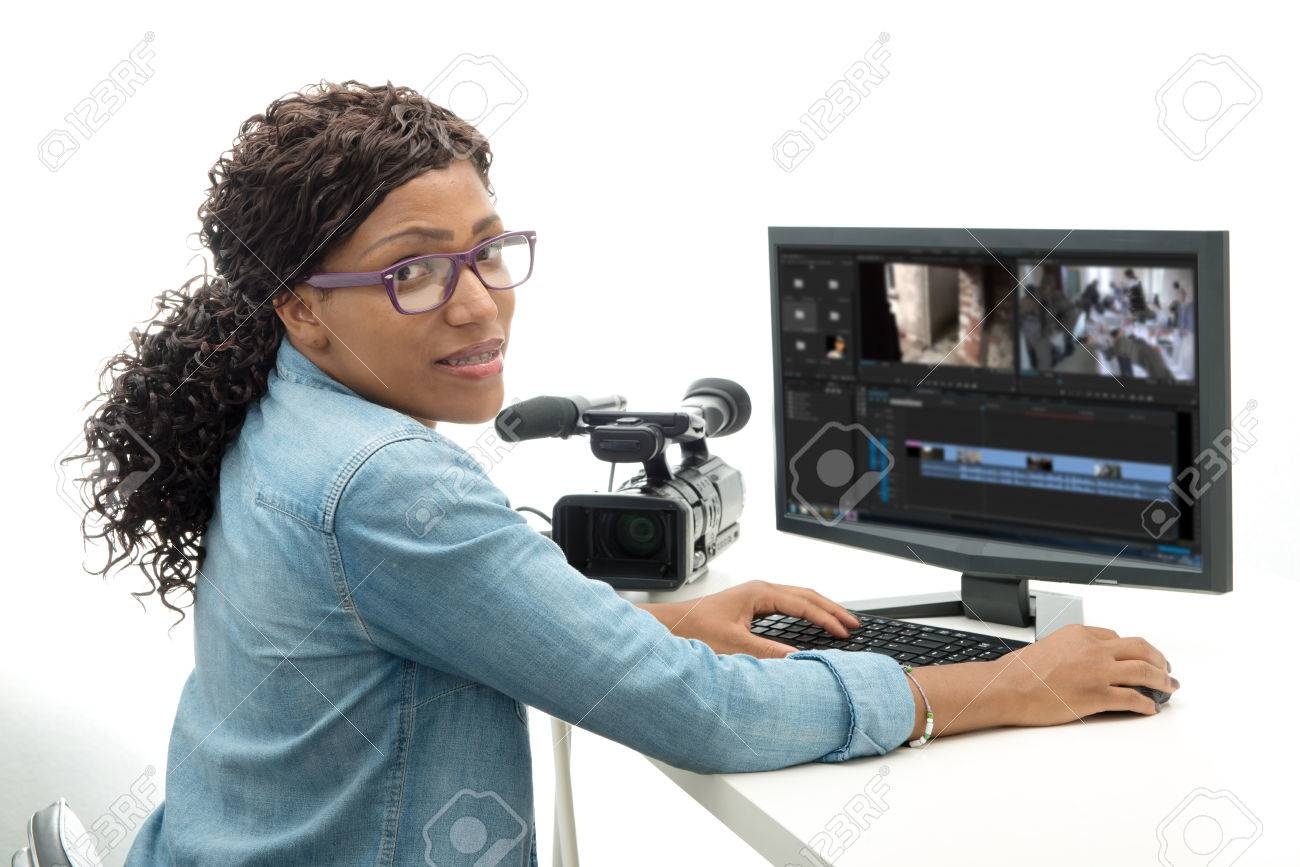 young African American woman video editor with computer and camcorder - 64319367