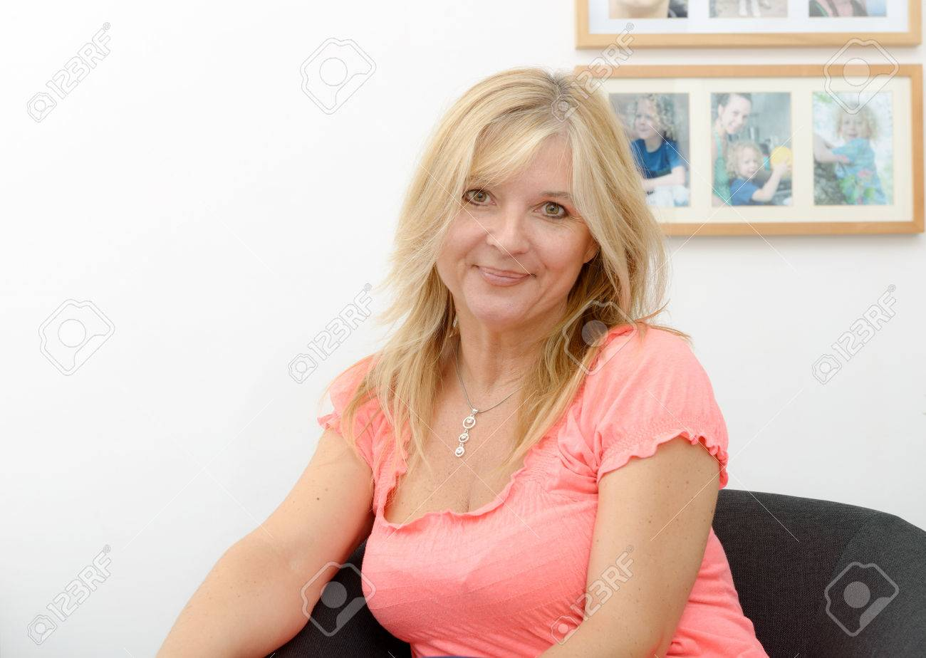 Portrait Of Blond Mature Woman Relaxing In Sofa Stock Photo 64320581