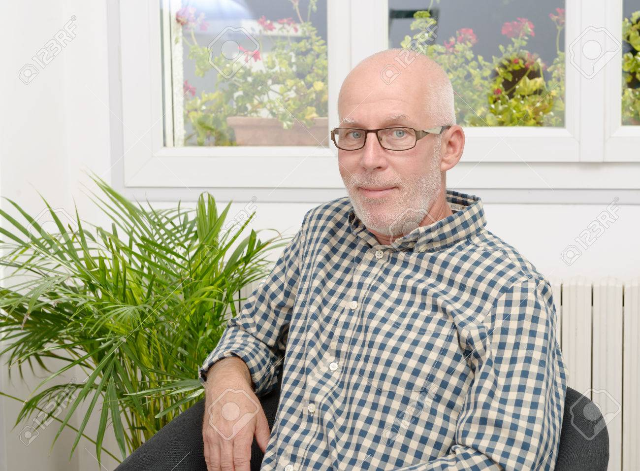 portrait of a smiling mature man with glasses at home - 64322188