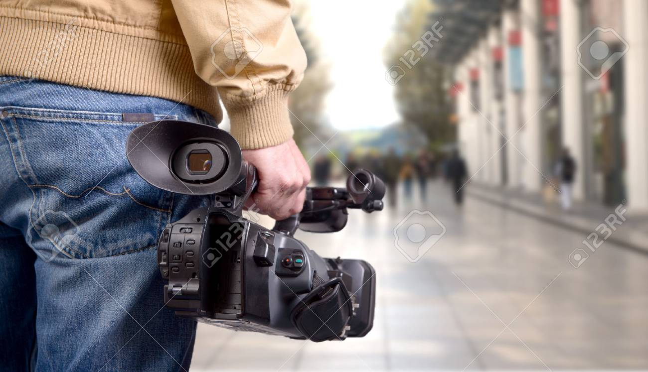 cameraman holding his professional camcorder in the street - 74960068