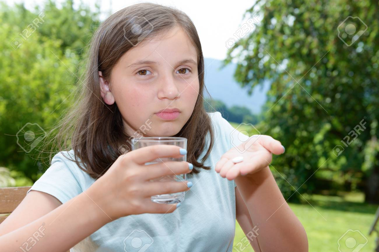 cute girl child taking pill with glass of water - 84156772