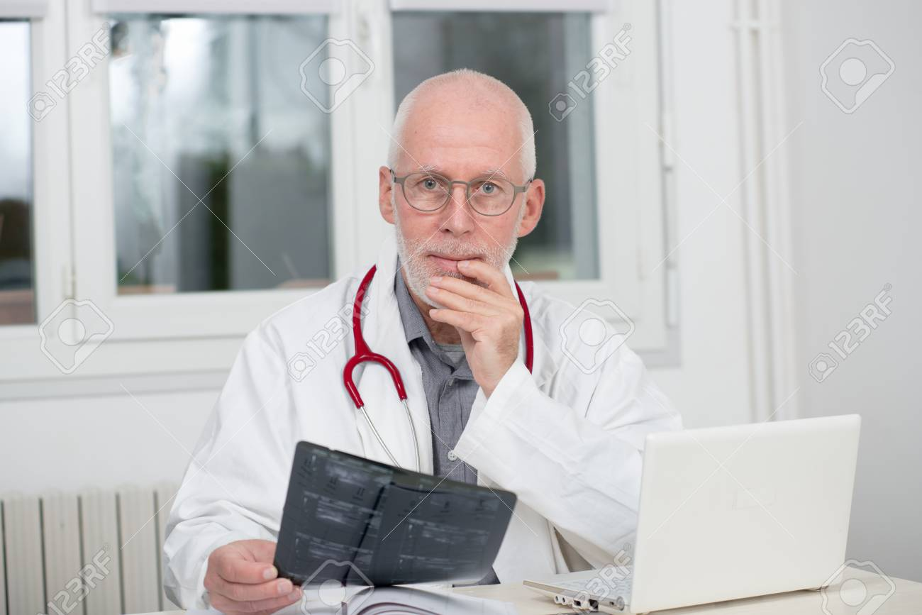 a mature doctor examining x-ray, at his office stock photo, picture