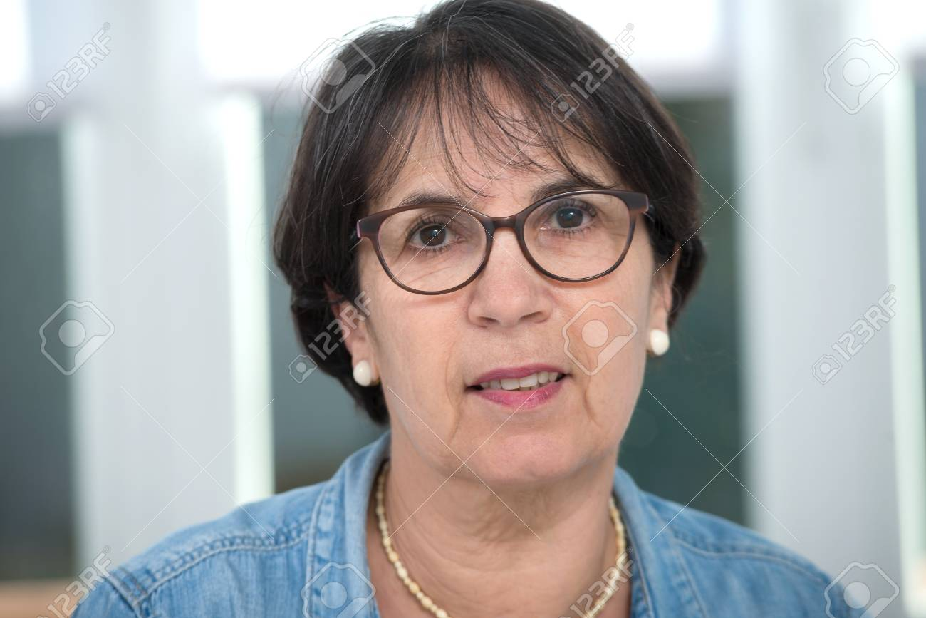 a portrait of middle age brunette with glasses - 94971207