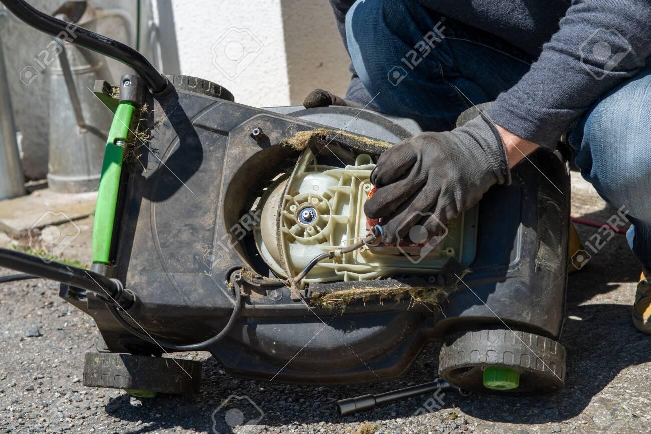 a man repairing an electric lawn mower - 123299307