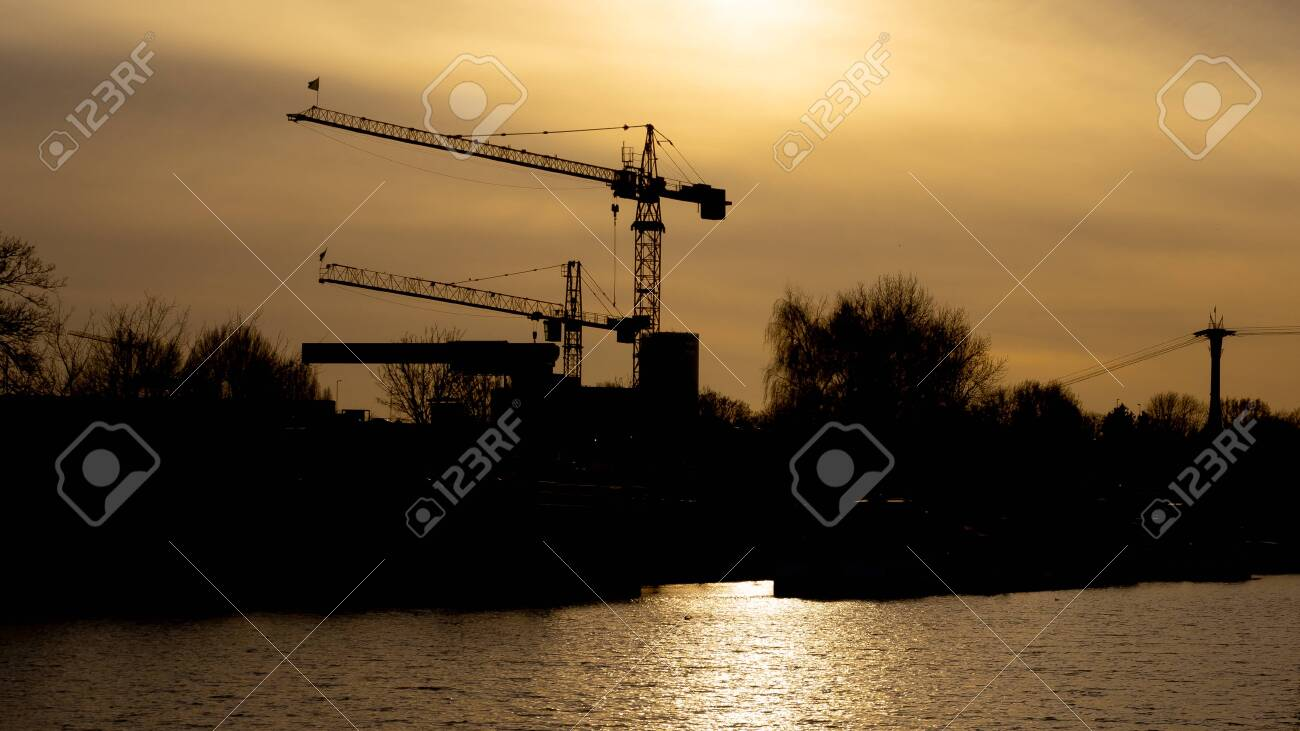 Two cranes in the sunset, in the front the river port M?hlheim, Cologne, Germany - 145688962