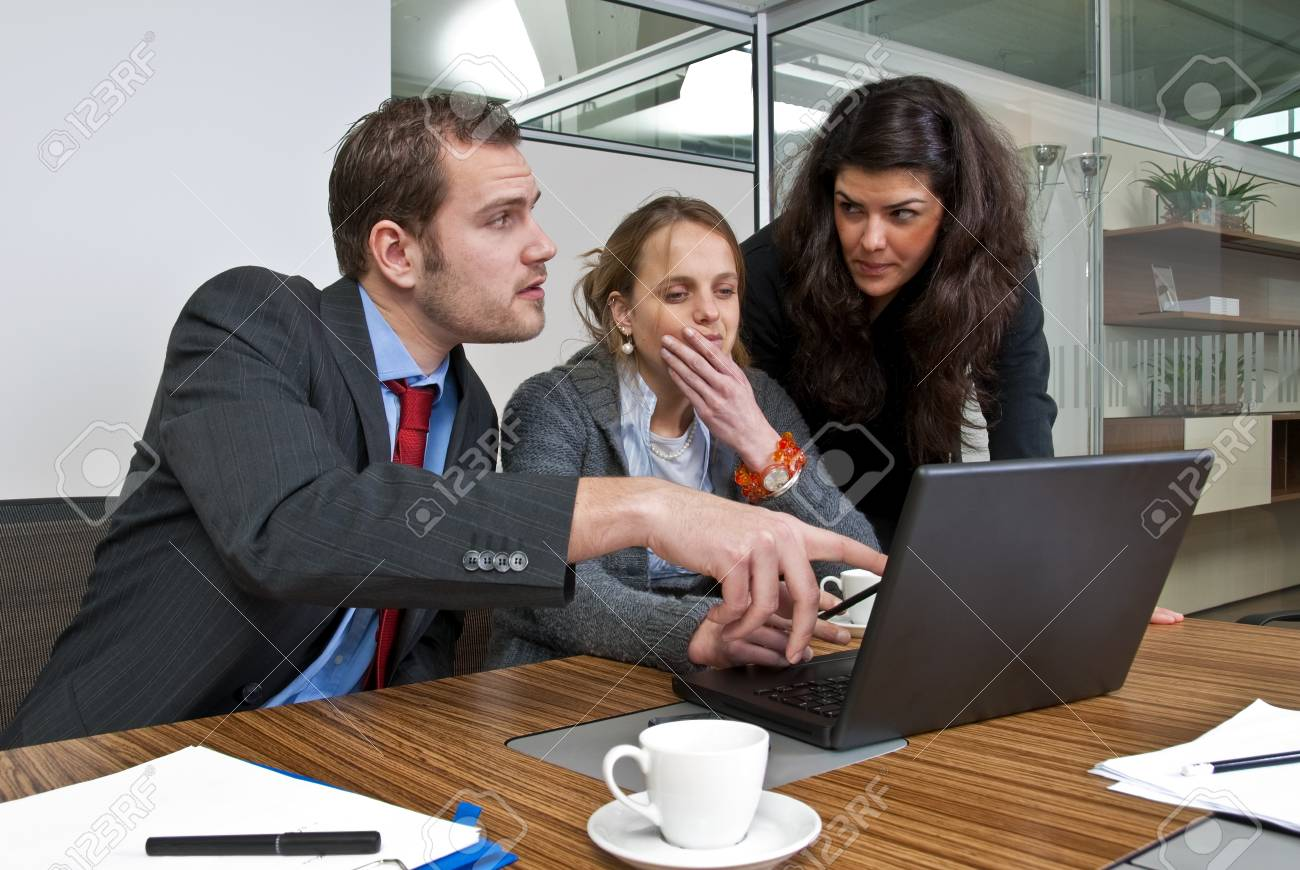 Three staff members discussing financial matters whilst browsing a laptop Stock Photo - 4259885
