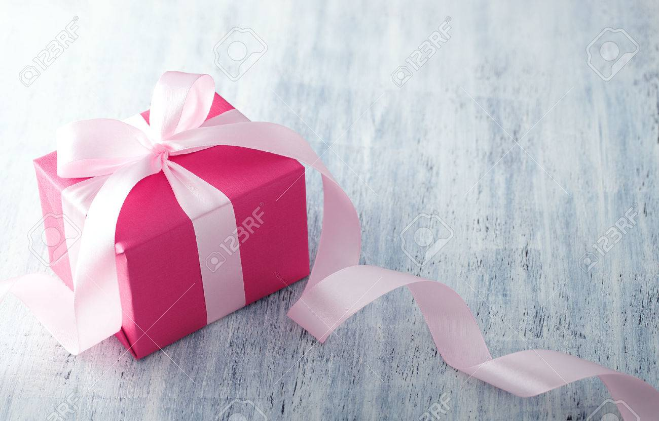 Pink gift box with ribbon on white painted wood background - 50994343