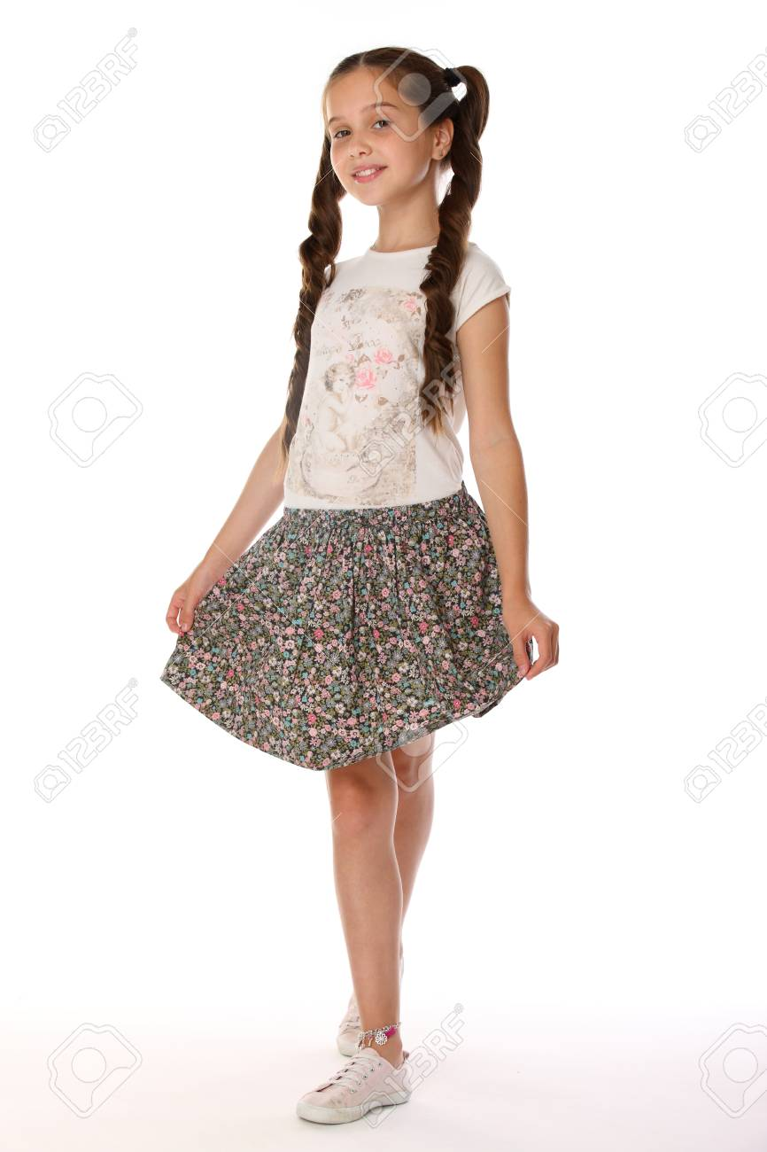 A little girl 12 years old posing in summer clothes. Charming pretty  slender young teenager