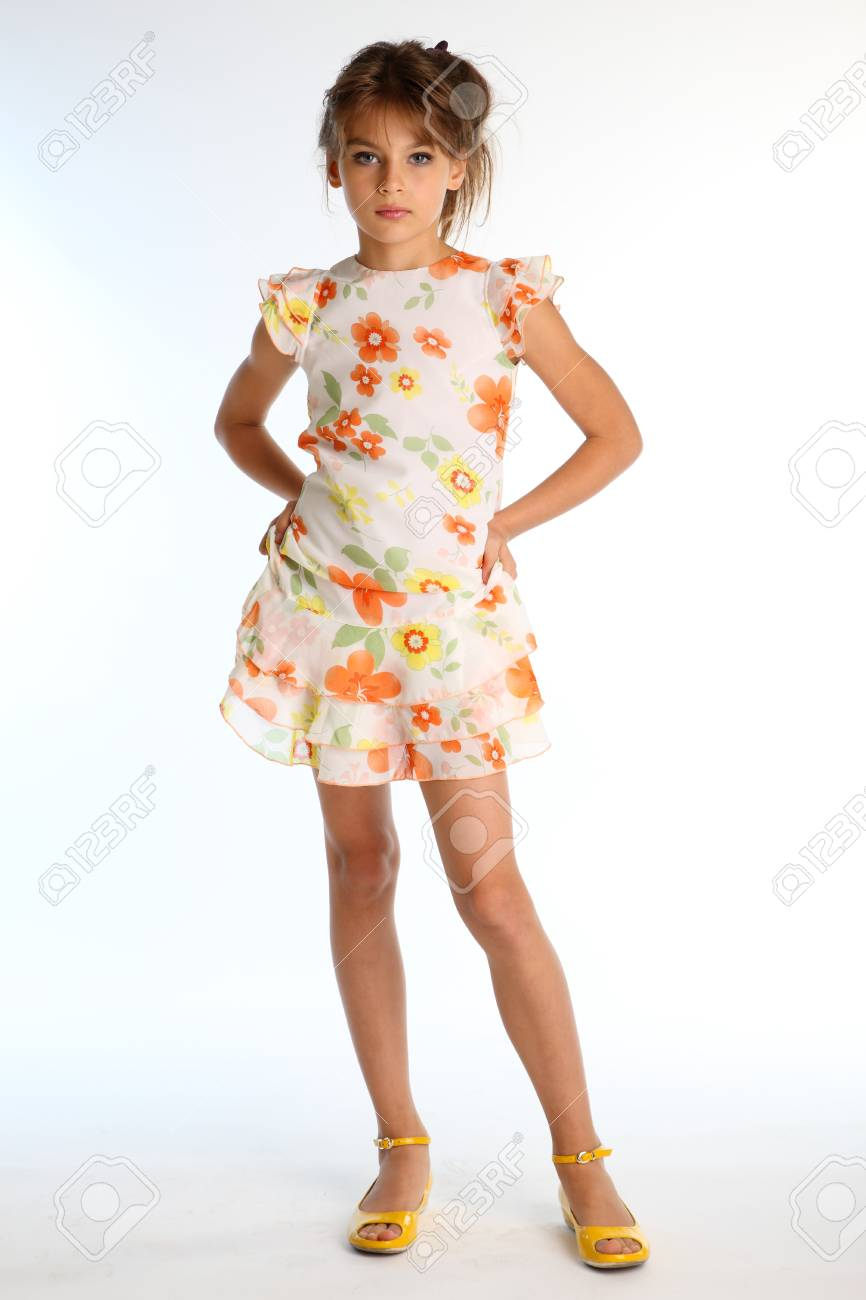 0e0c4ff0761c Tanned little girl in a bright summer dress is standing on white  background. Attractive child with a slender body and long bare legs in  yellow shoes.