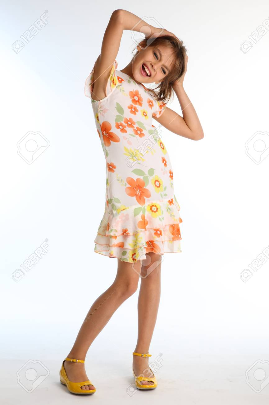 1418df39f1a2 Emotional little girl in a bright summer dress is standing on white  background. Attractive child with a slender body and long bare legs in  yellow shoes.