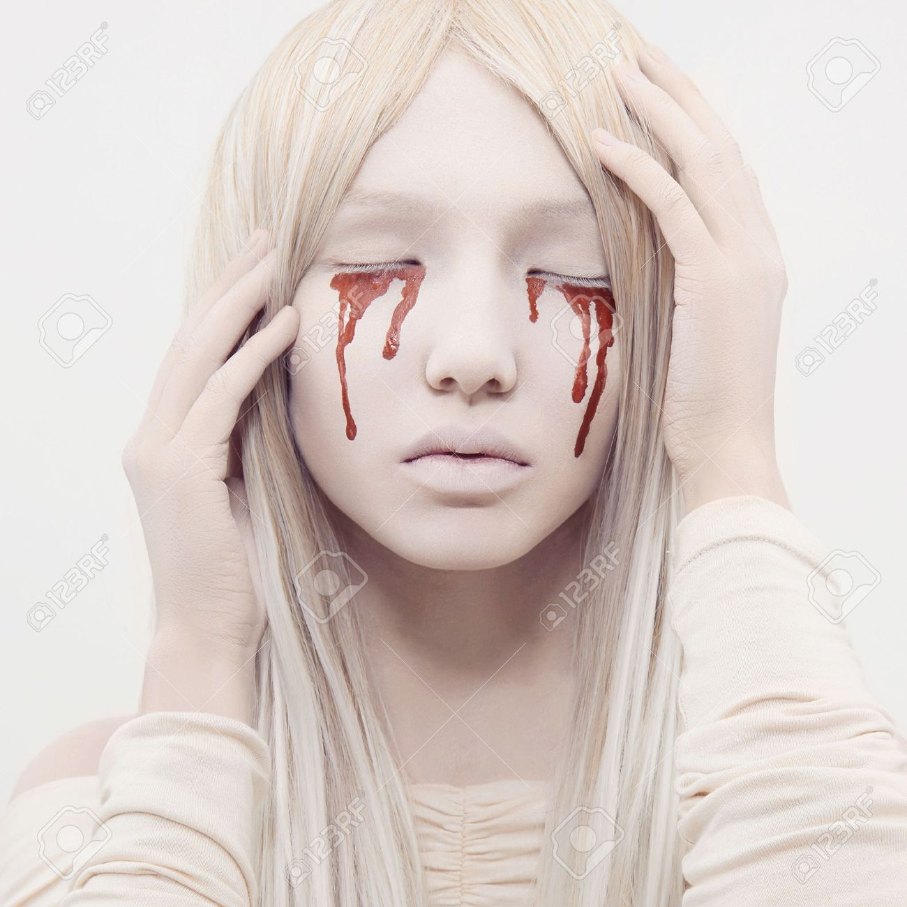 Beautiful young woman with blood from her eyes blond sexy halloween girl horror