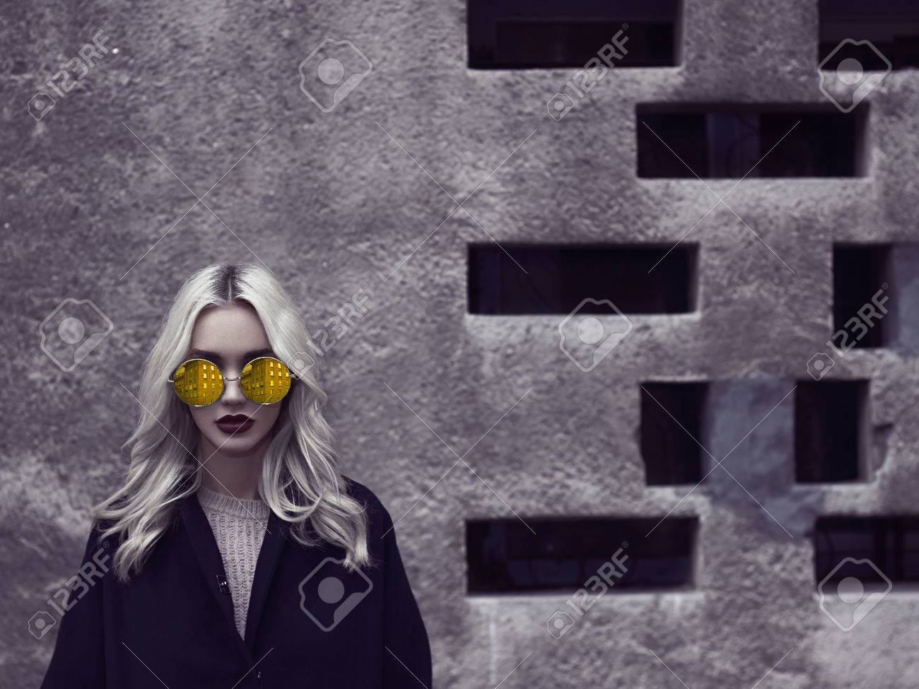 Portrait of fashionable blonde girl wearing a black top coat and colorful glasses.young woman walking in city - 67520890