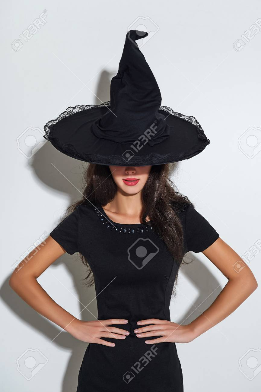 charming brunette witch in black dress and a hat. halloween