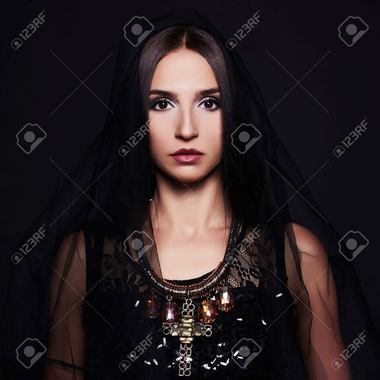 Beautiful woman with black veil portrait studio shot brunette model girl gold jewelry
