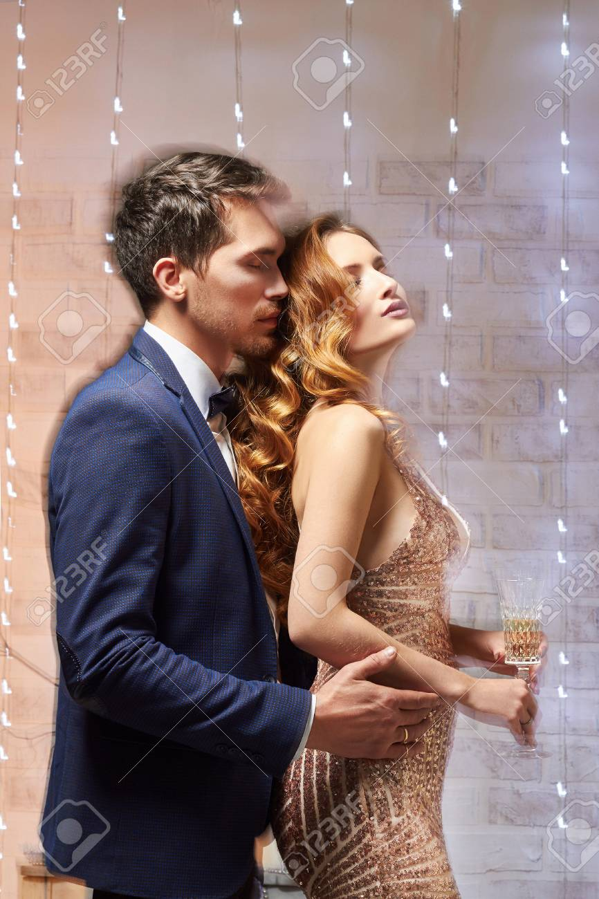 41ae5430c004b Stock Photo - Young couple in love.Cheerful young couple in elegant evening  dresses. Fashion, glamour.hugging in christmas decorated interior