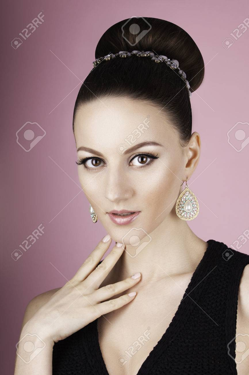 portrait oflady with clean make up and hair bun in the pink