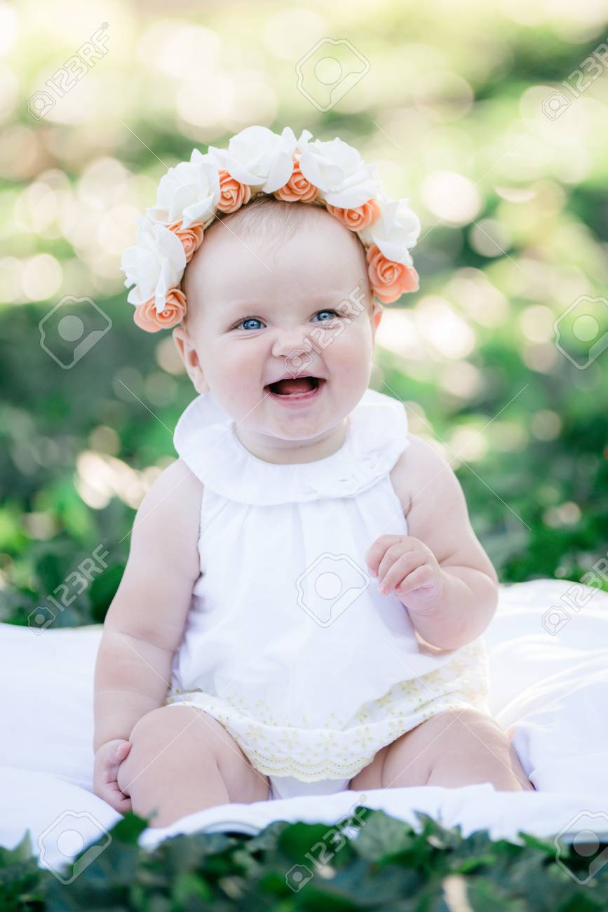 Baby girl 8 months old portrait looking up to camera outdoors in sunlight stock photo