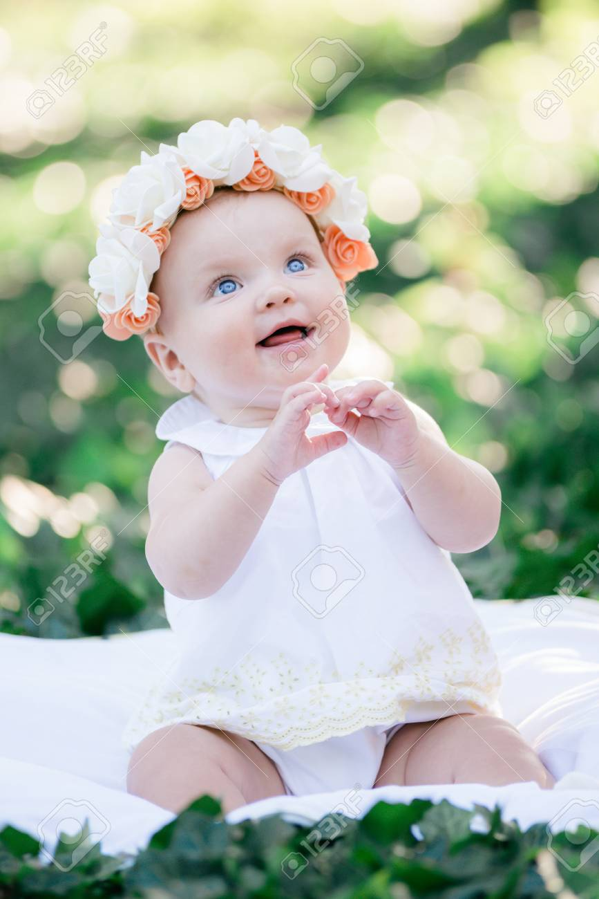 Baby girl 8 months old portrait outdoors in sunlight stock photo 86954243