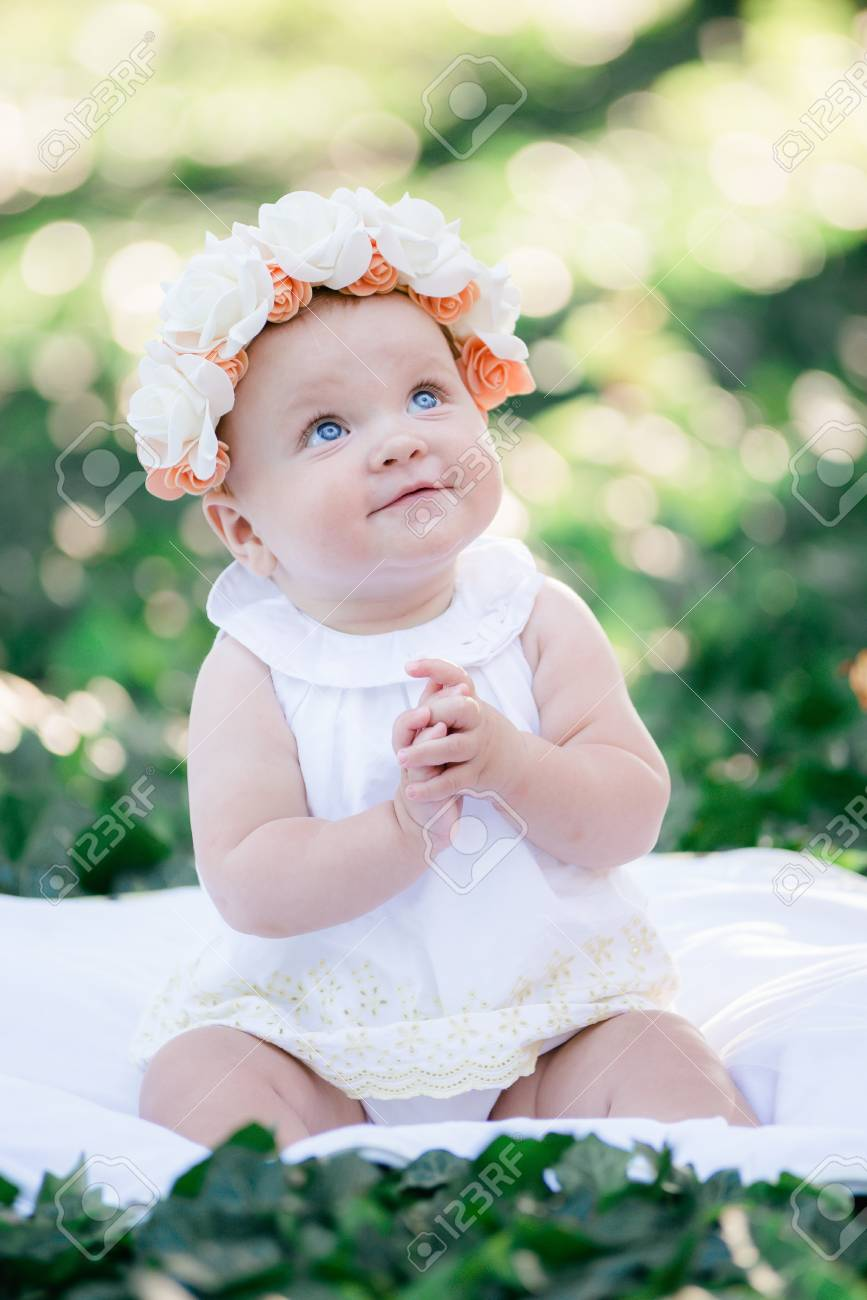 Baby girl 8 months old portrait outdoors in sunlight stock photo 86954244