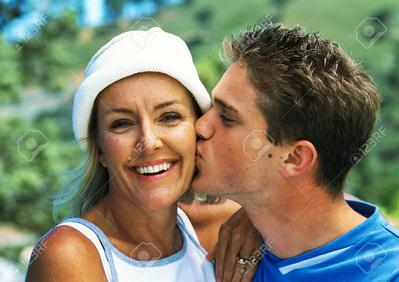 Teenage boy kissing mature woman's cheek, close-up, portrait Stock Photo -  89563414