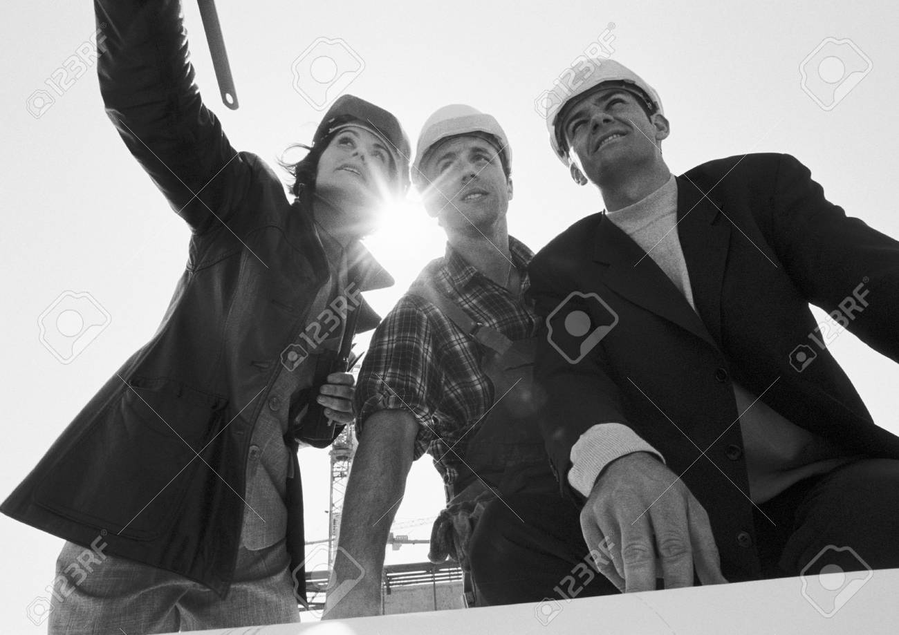 Two men and woman wearing hard hats, low angle view, b&w