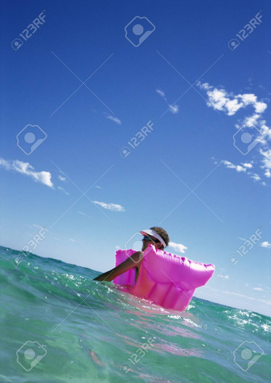 Man Floating On Air Mattress In Sea Stock Photo