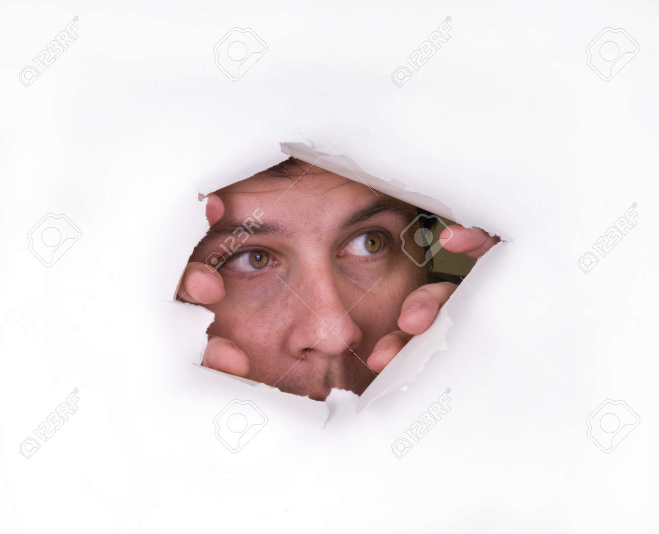 A man looks through a hole in the paper - 155940186