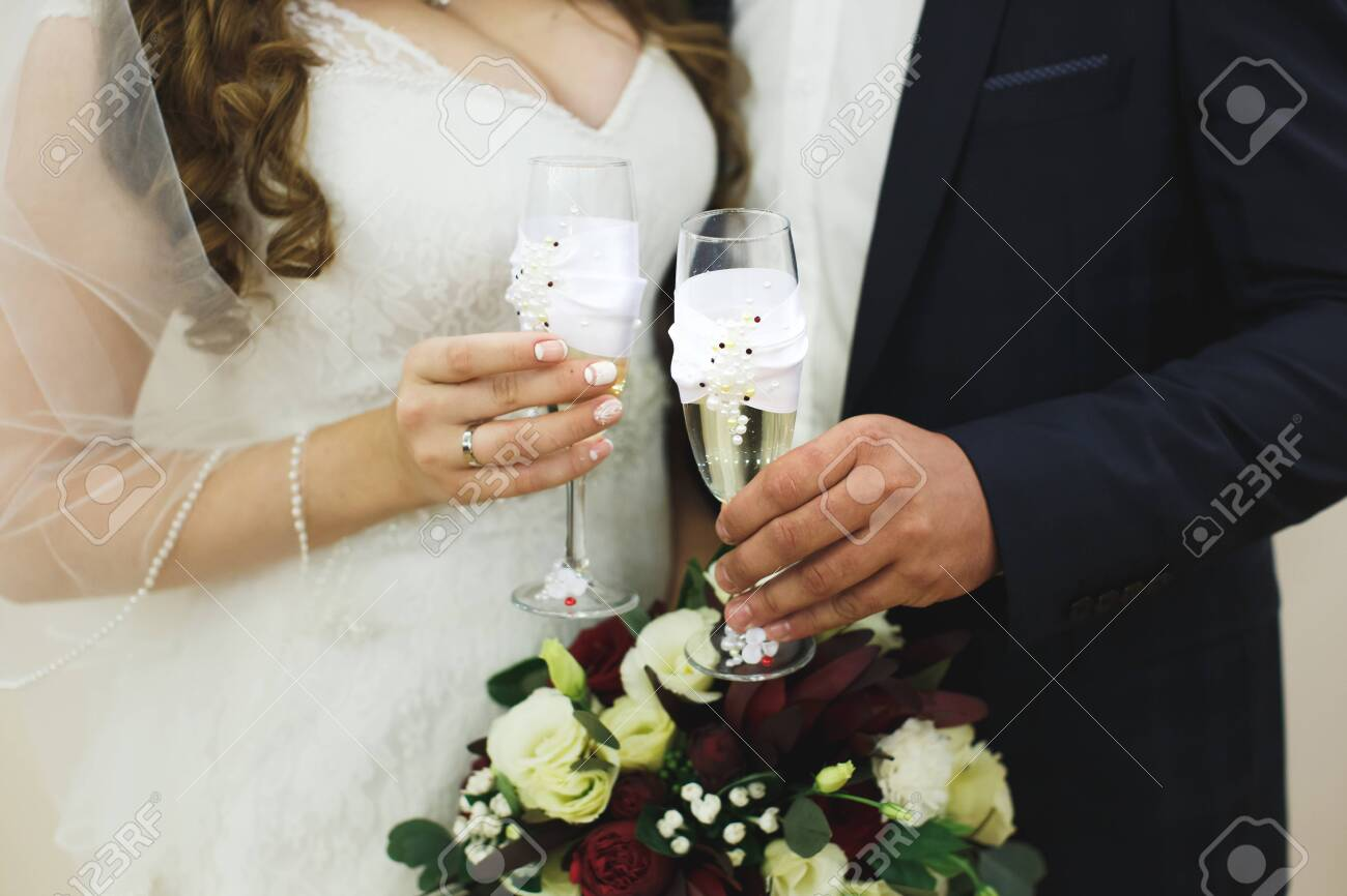 bride and groom holding beautifully decorated wedding glasses with champaign - 142703972
