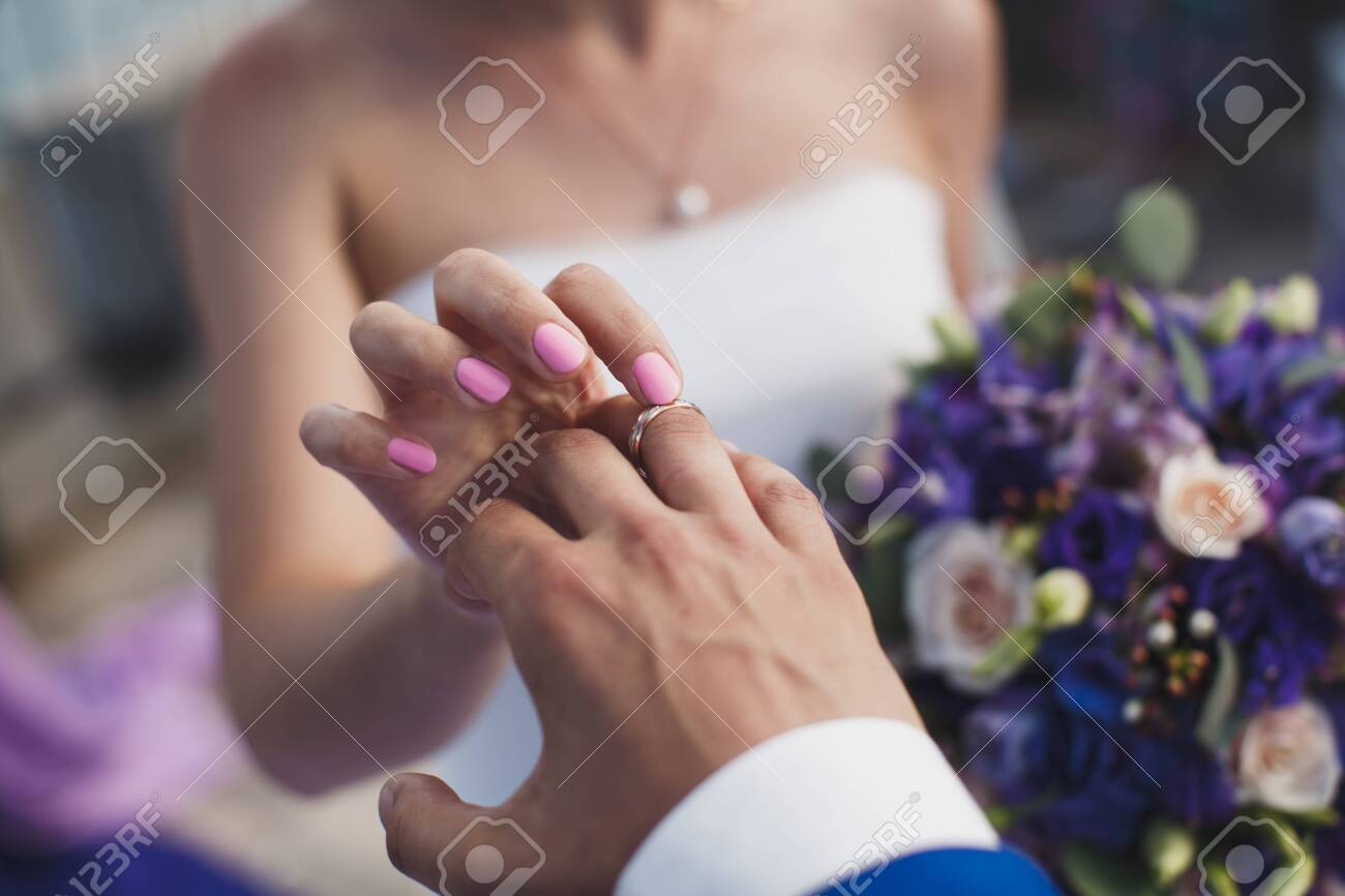 bride and groom put on the finger a wedding ring. - 143183680
