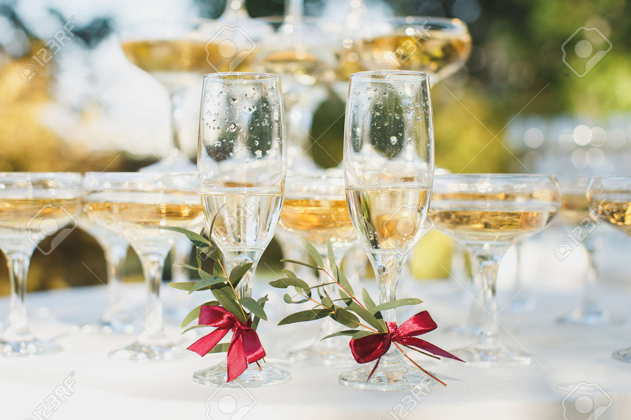 Beautiful hill with champagne at the Banquet for the newlyweds.Glasses of the bride and groom. - 142709374