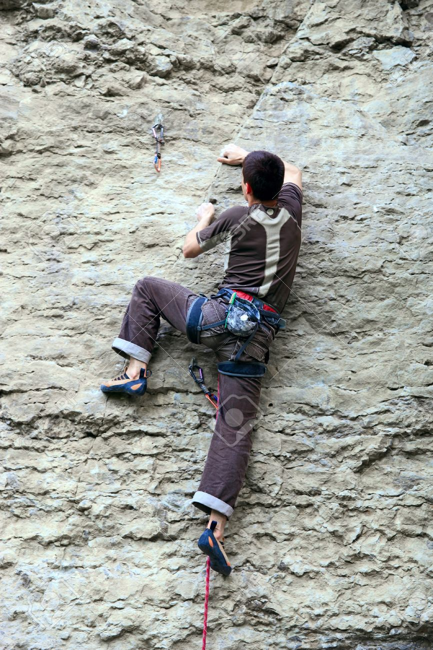 Rock climber climbing up a cliff Stock Photo - 16627098