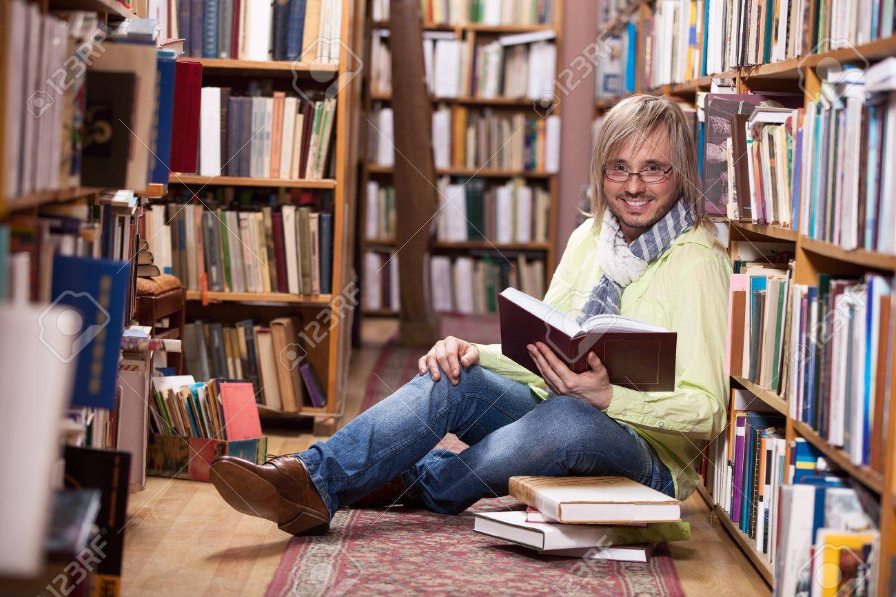 Handsome man reading book while sitting on floor in library Stock Photo - 17570905
