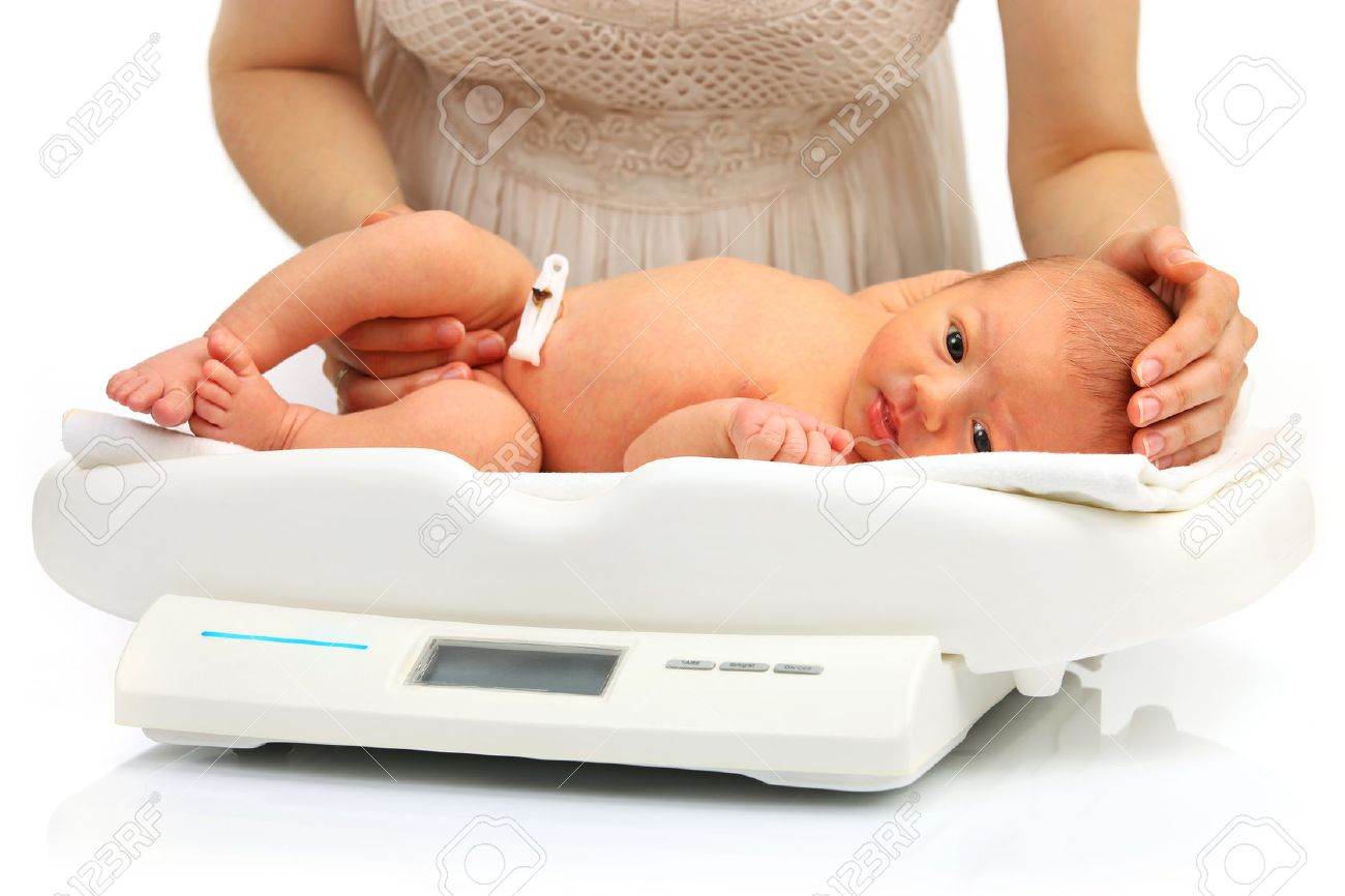 Mother And Her Newborn Baby On A Weight Scale Over White ...