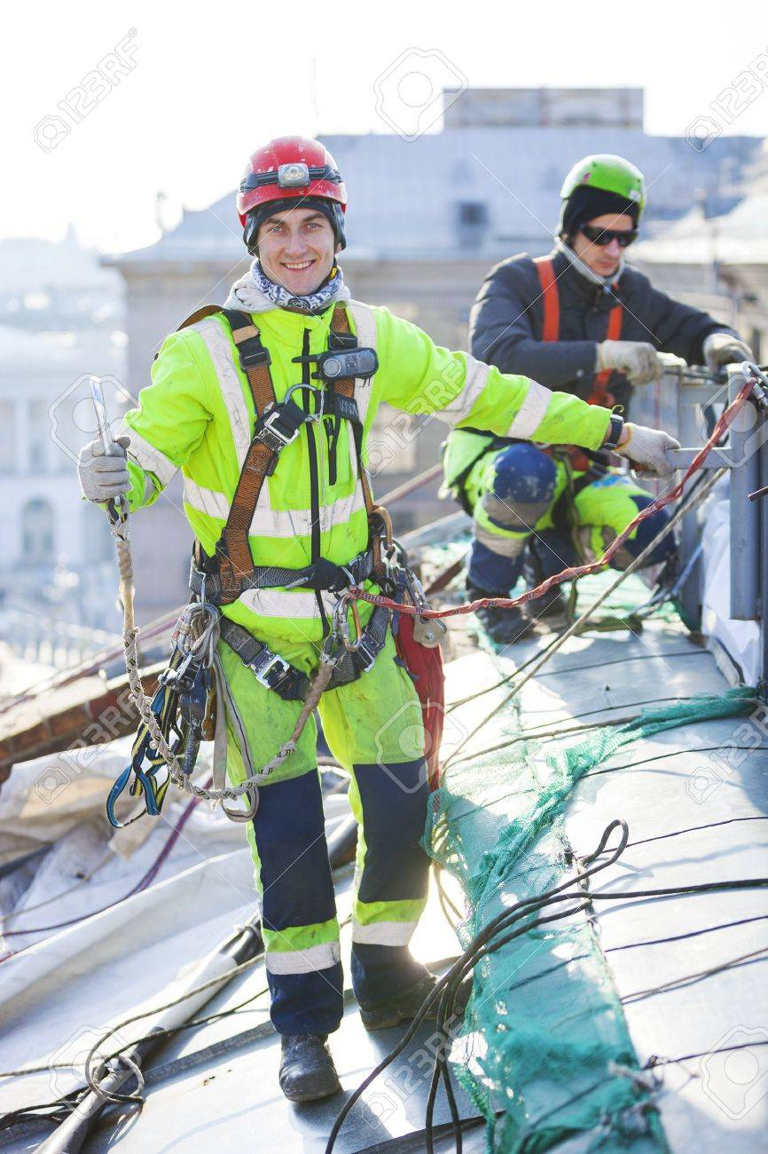 Industrial climbers working on a roof of a building - 38469596