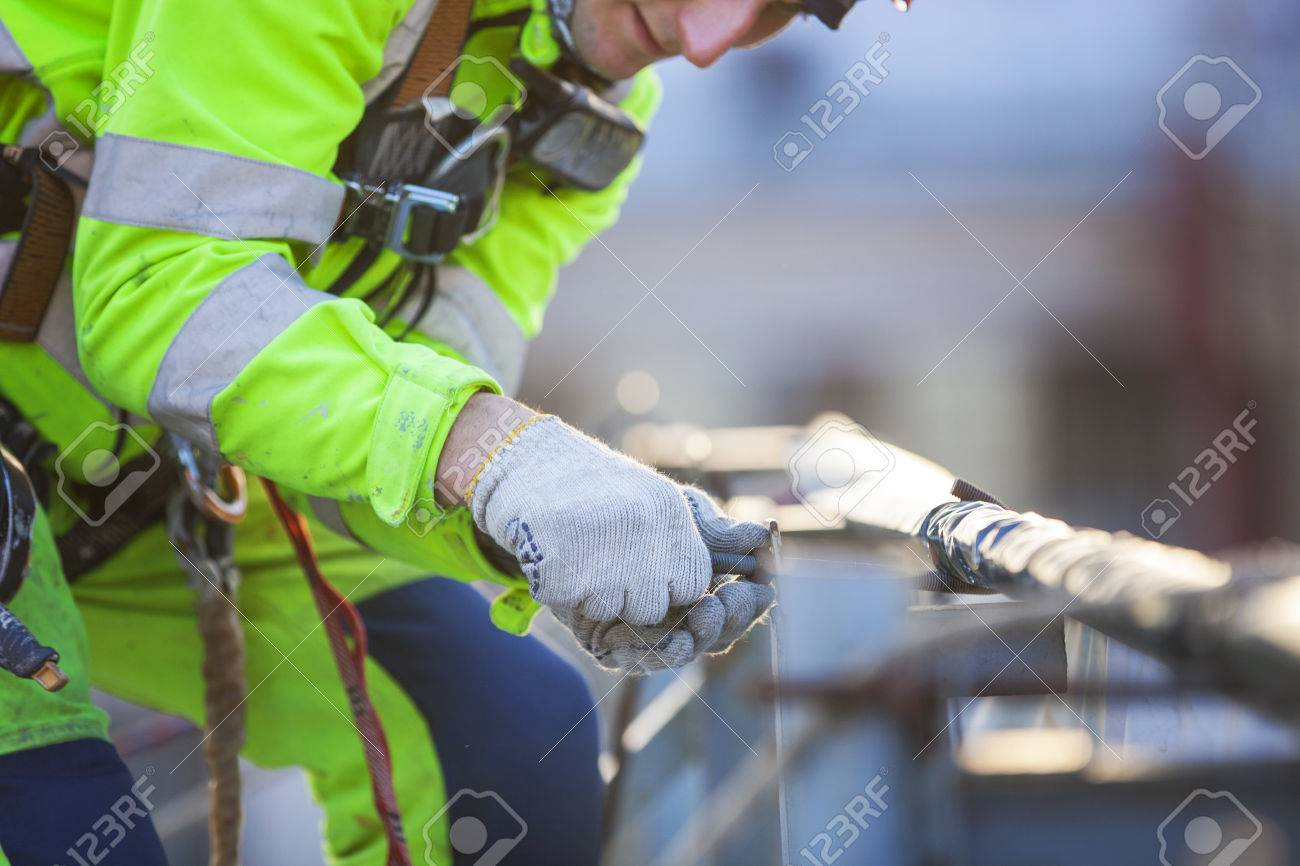 Closeup of industrial climber working on roof of building - 39246718