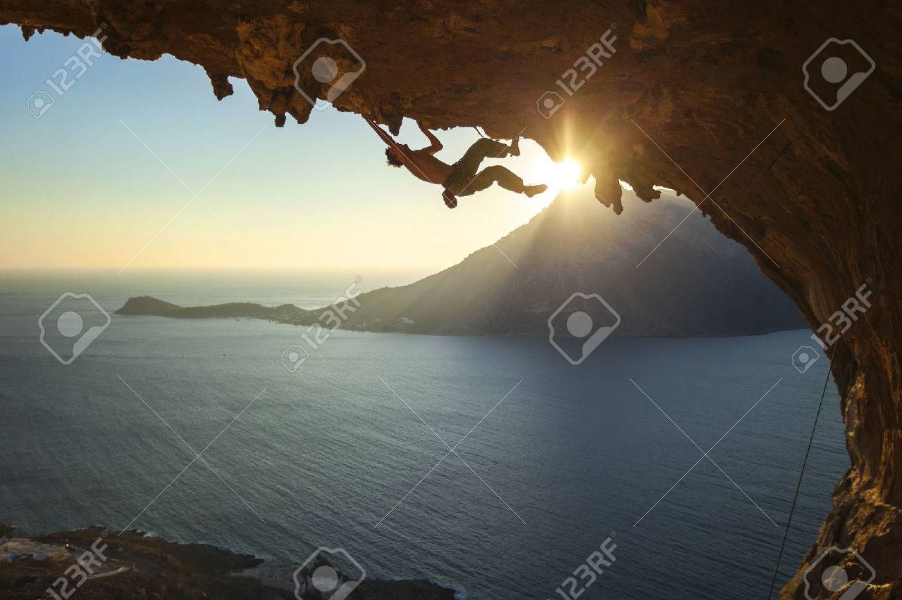 Male rock climber climbing along a roof in a cave at sunset - 49280873
