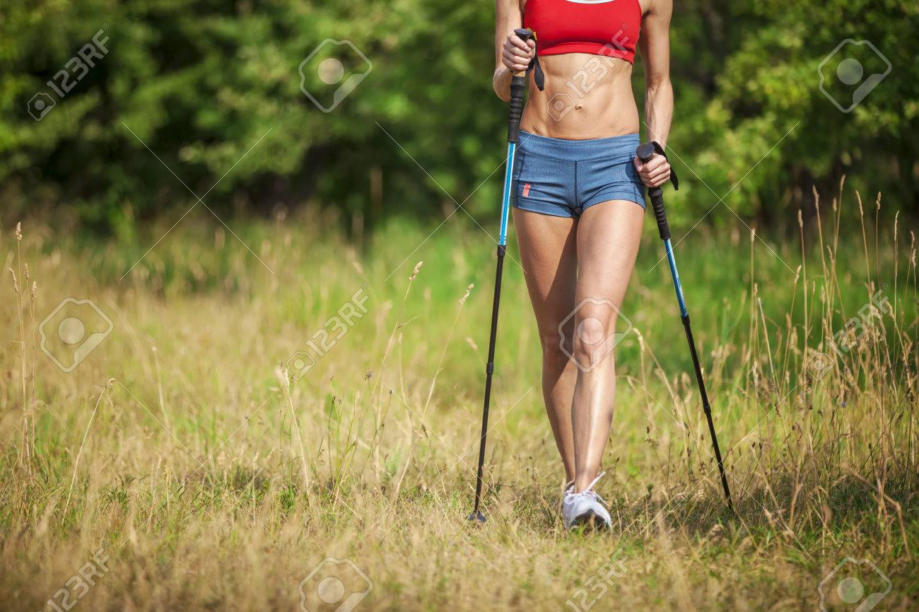 Fit young woman hiking with nordic walking poles in summertime - 48996437