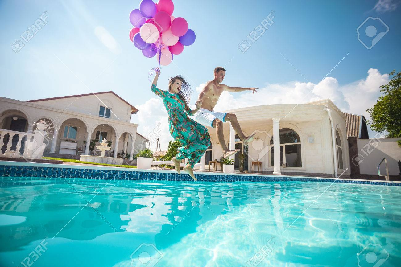 Happy young couple jumping into the pool while holding a bunch of balloons - 48996569