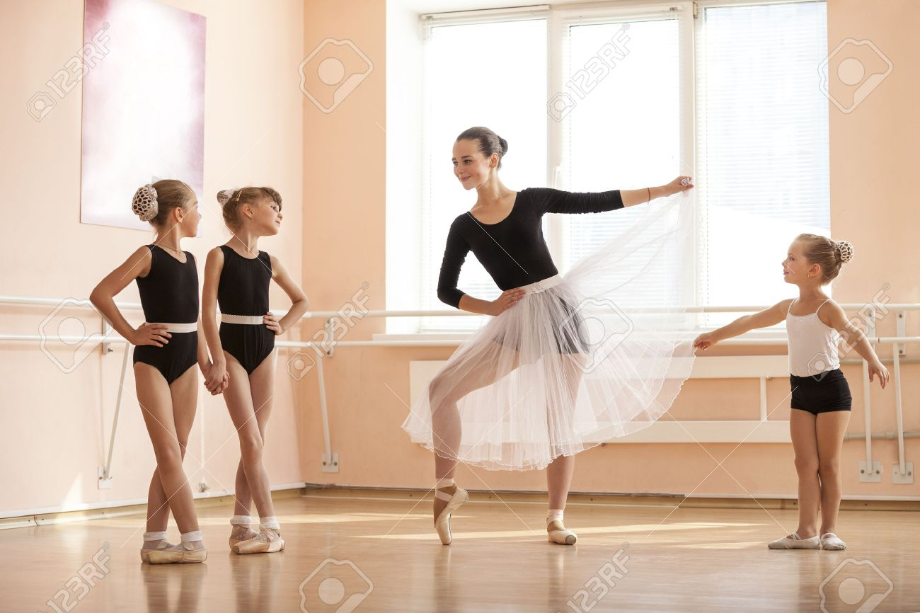 Young girl warming up and talking to younger classmates at ballet dancing class - 48996591