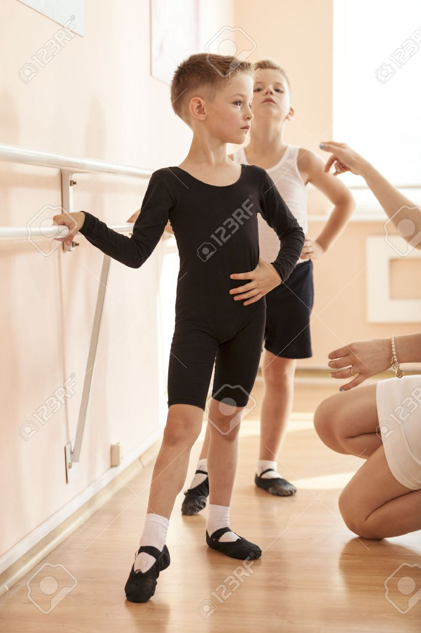 Young boys working at the barre in a ballet dance class. Teacher adjusting the position of one of them. - 48931345