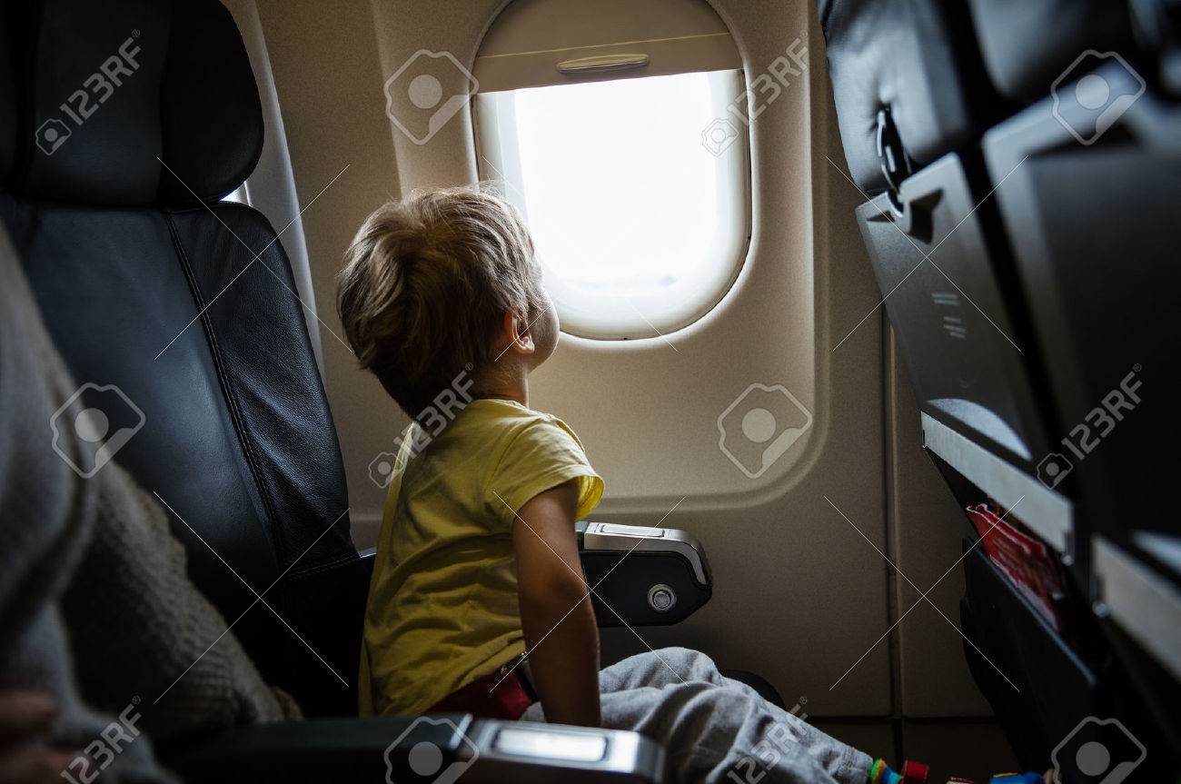 Little boy looking out of window in airplane - 57956605