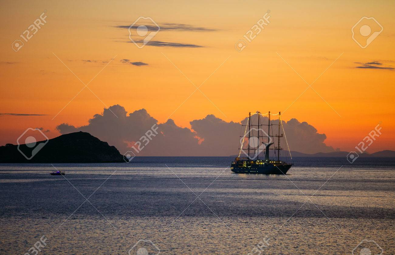 View of cruise sailing ship and small ferry boat by rocky coast at sunset - 74710007
