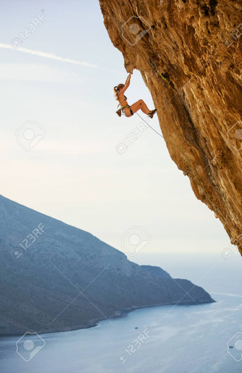 Caucasian young woman in bikini climbing challenging route on overhanging cliff - 122338162