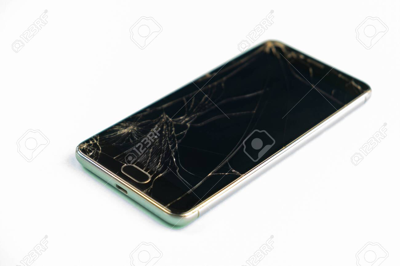 Mobile phone with broken black screen, top view. Distressed damaged smartphone in pale green background, shallow depth of field - 140117275